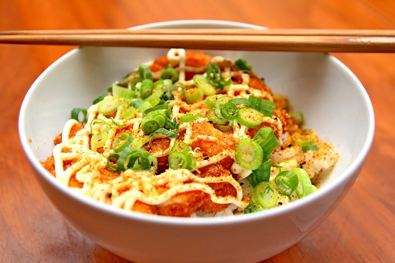 Chinese noodles with red pepper in white bowl.