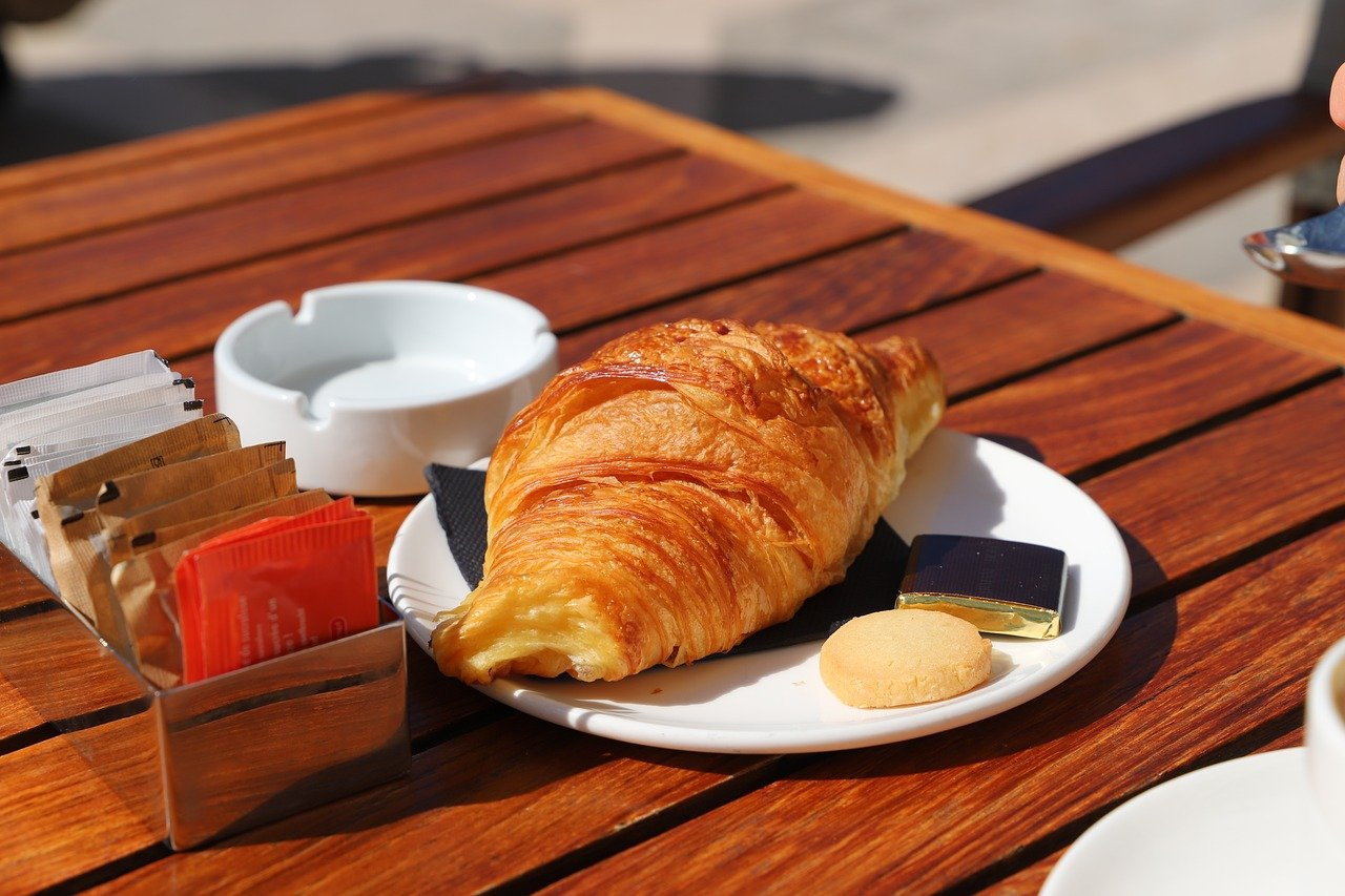 French cafe with large wood table and croissant on white plate.