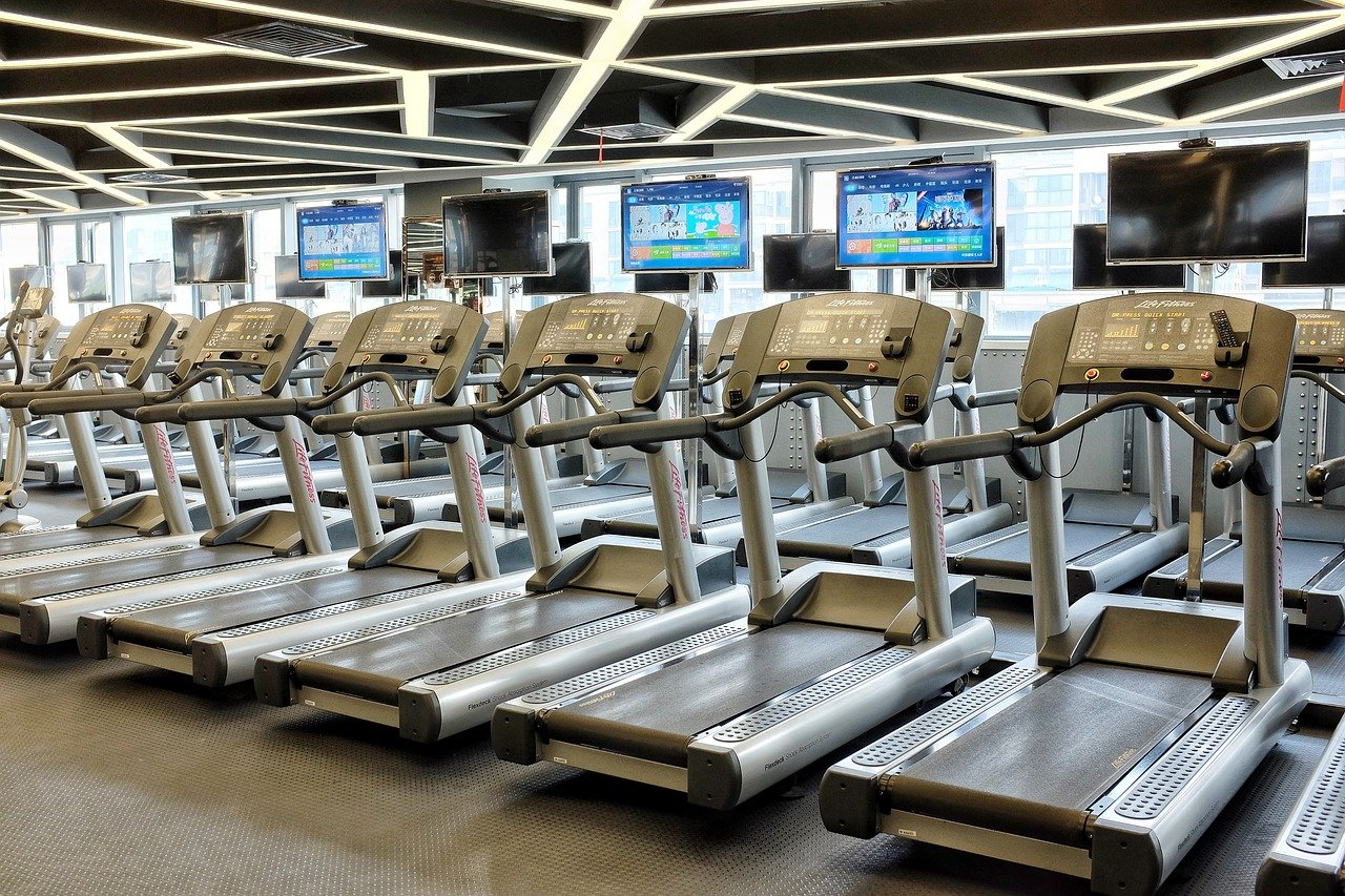 Gym with empty treadmills and TV screens.