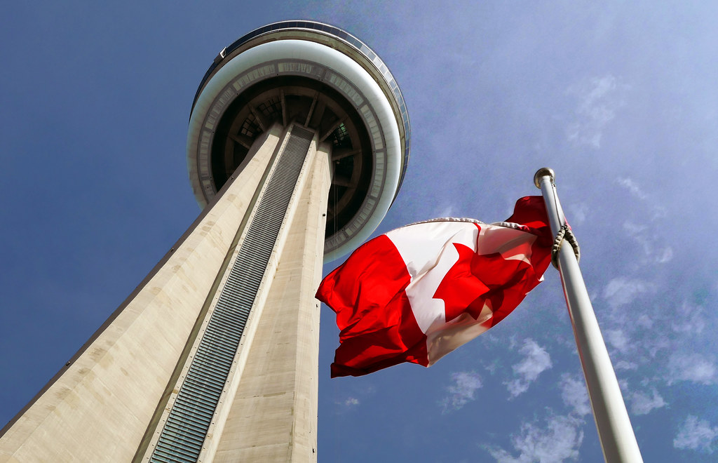 Looking up at CN Tower and Canada flag.