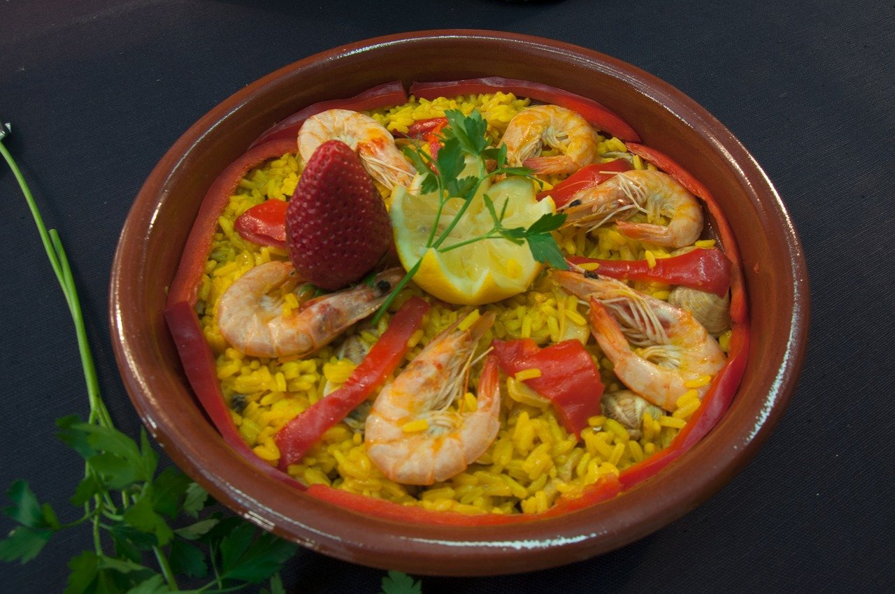 Paella in brown bowl with rice.