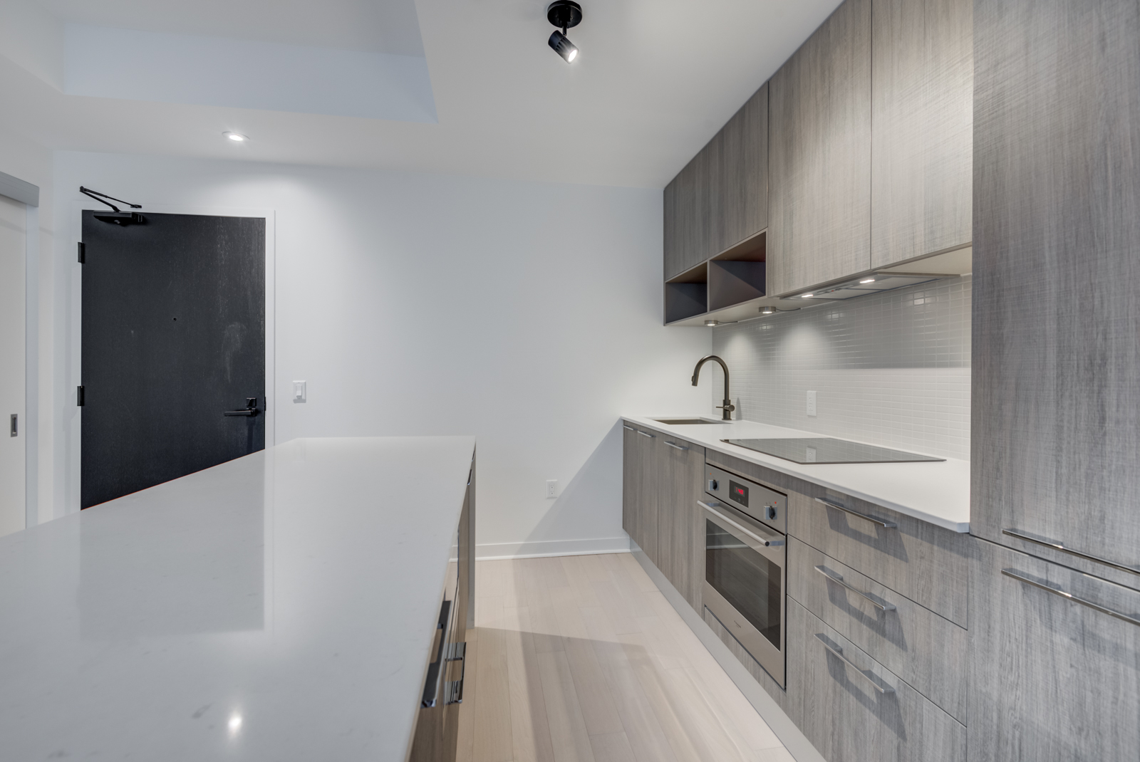 Kitchen cabinets, drawers and appliances with track-lighting and under-cabinet lighting.