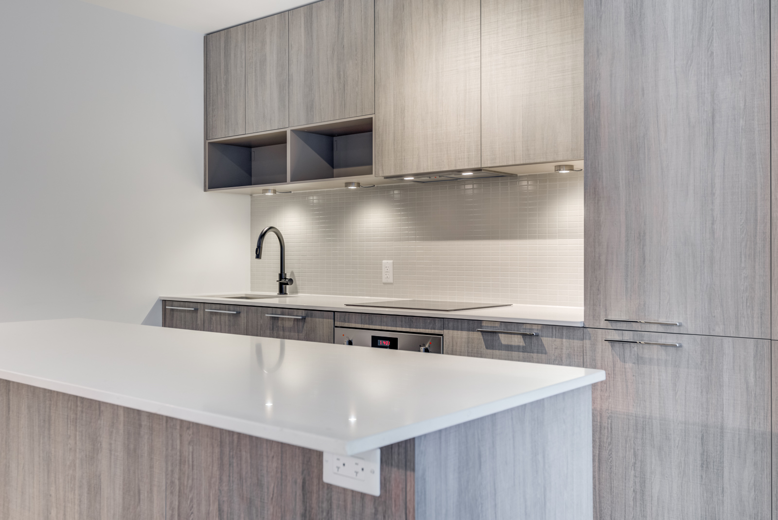 Close up of kitchen island with white counter-top and brown base, as well as kitchen cabinets and back-splash.