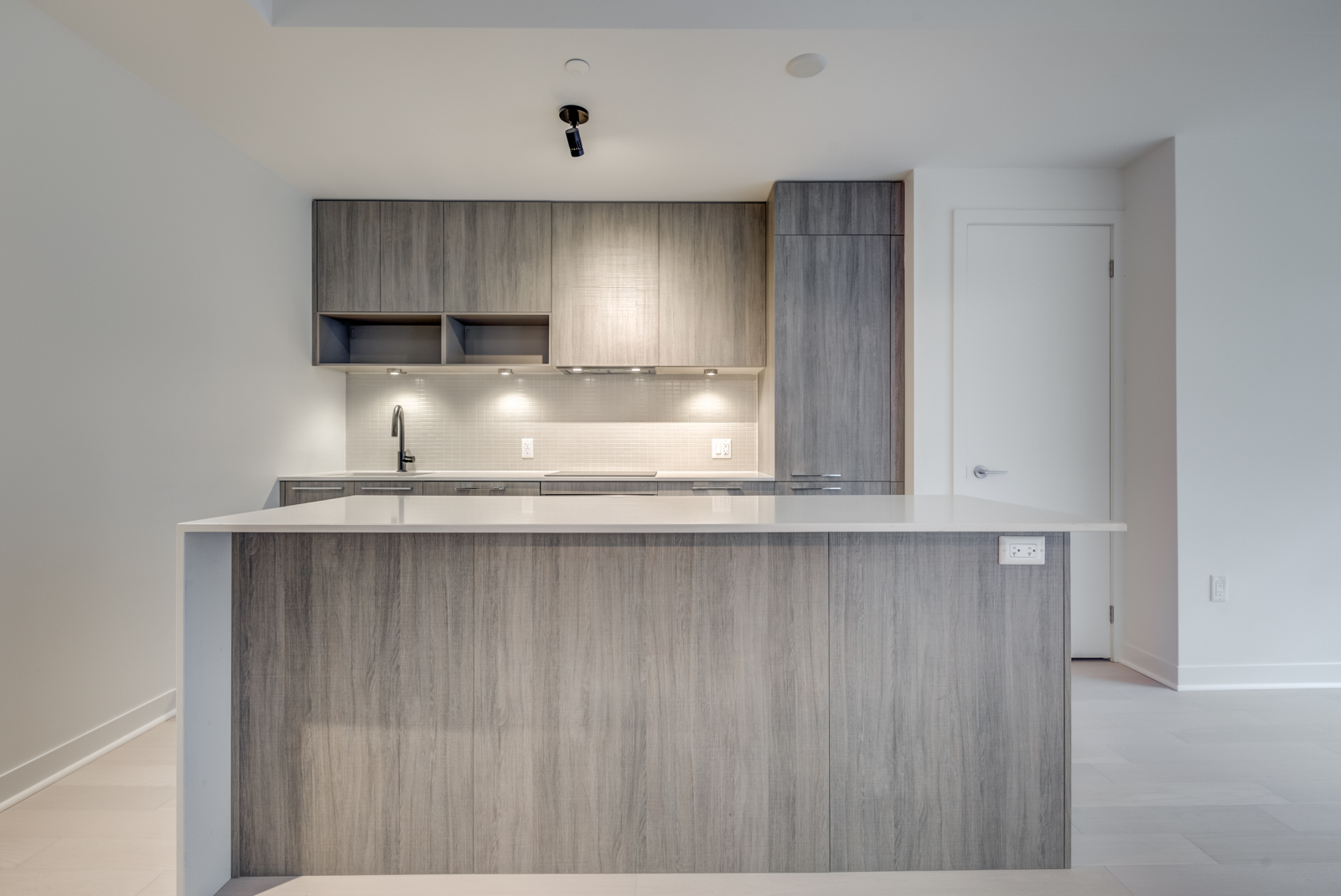 Centered view of kitchen island in foreground and cabinets in background.
