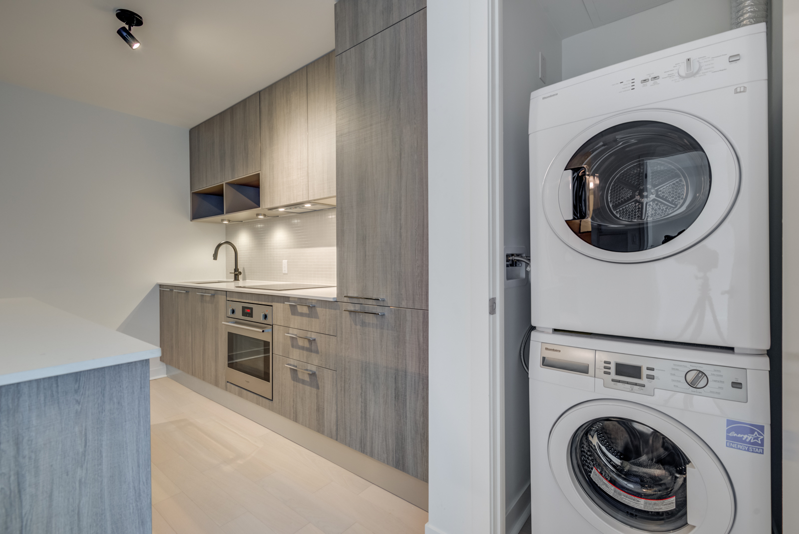 Open laundry closet showing stacked white washer and dryer plus kitchen to its left.