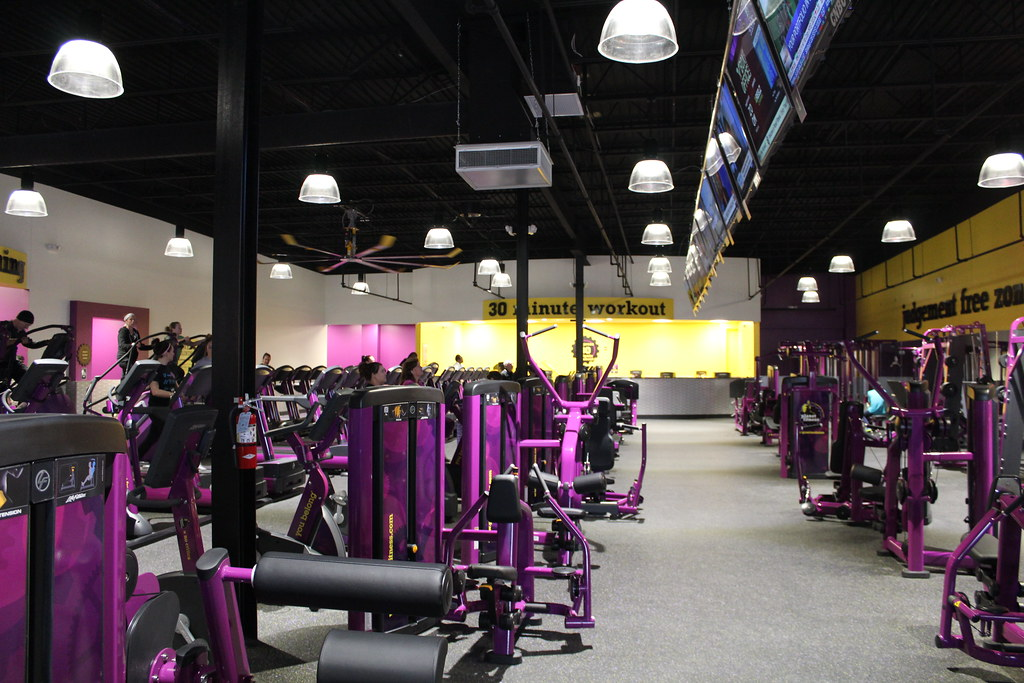 Planet Fitness purple gym equipment, yellow walls and huge lights.