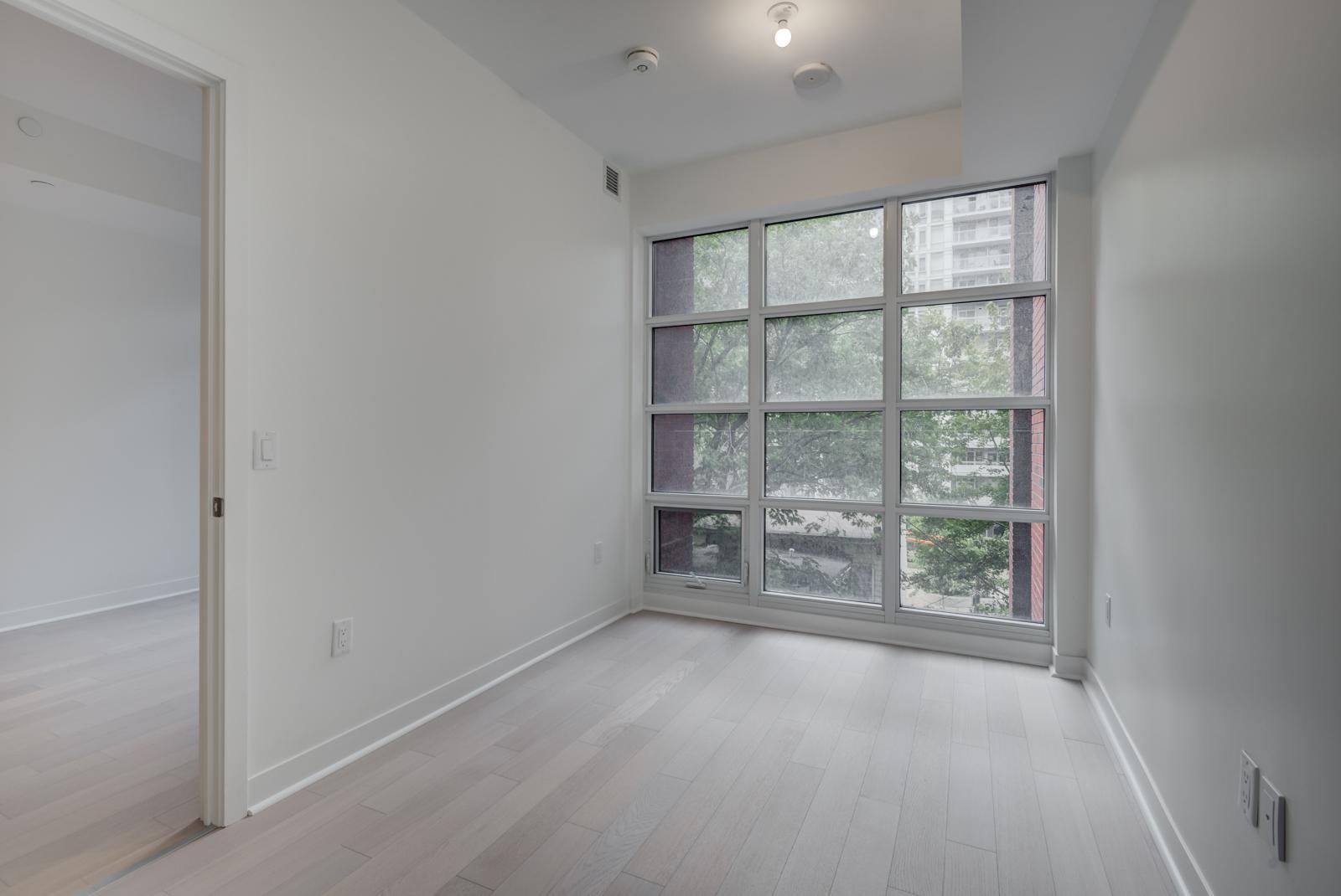 Empty master bedroom with floor-to-ceiling windows.