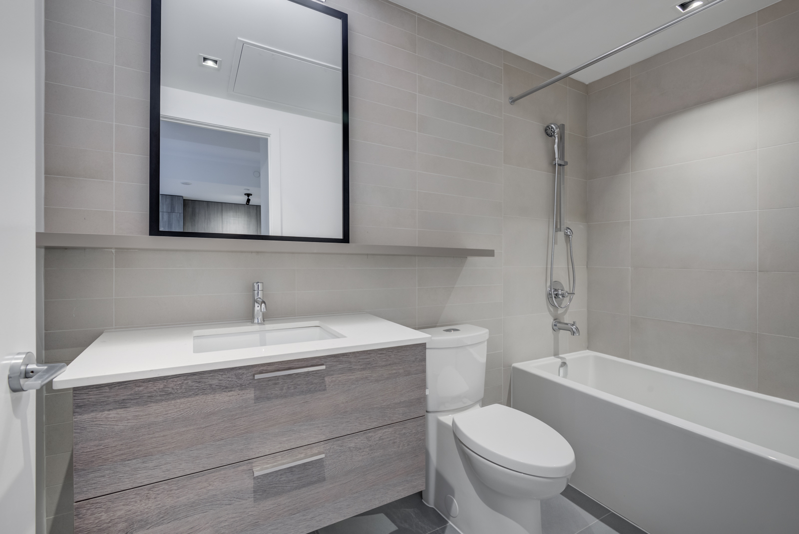 4-piece bathroom with white soaker tub, toilet, vanity, mirror and brown cabinets and tiles.