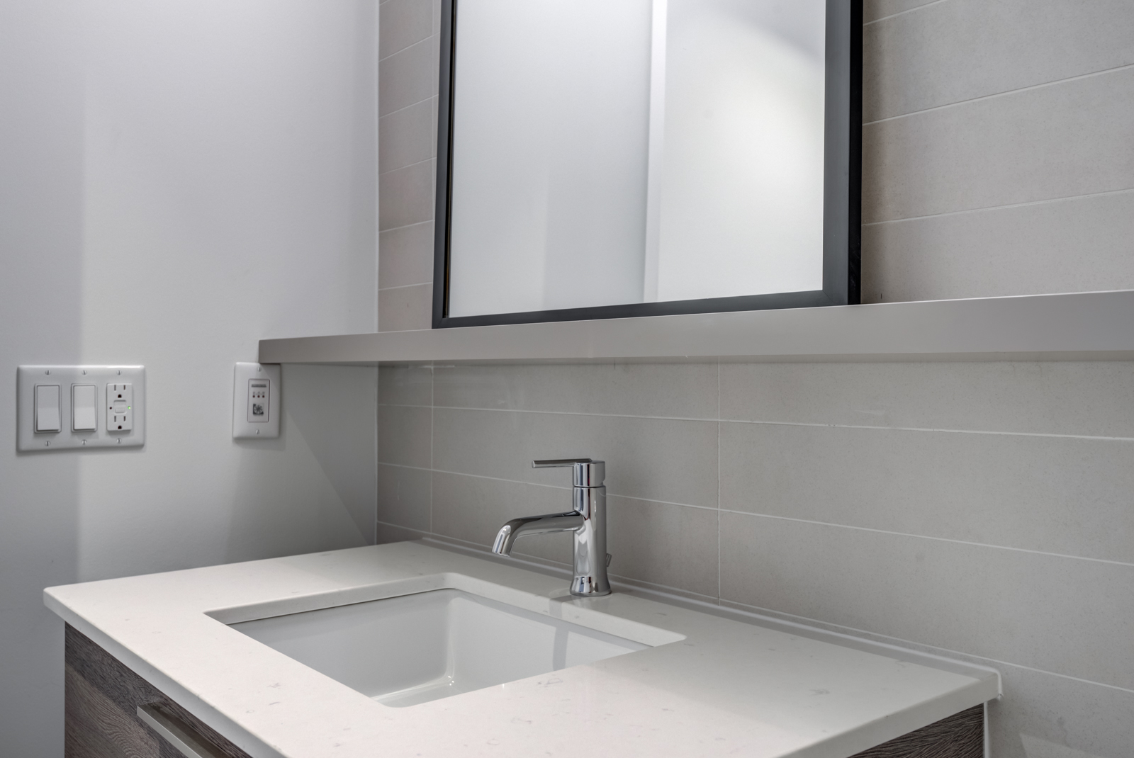 Close up of sink with white counter, shelf and mirror.