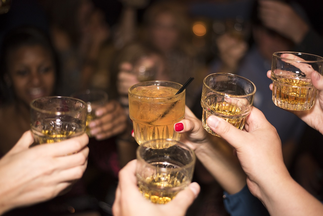 Close up of hands holding glasses of gold-coloured alcohol in celebration.
