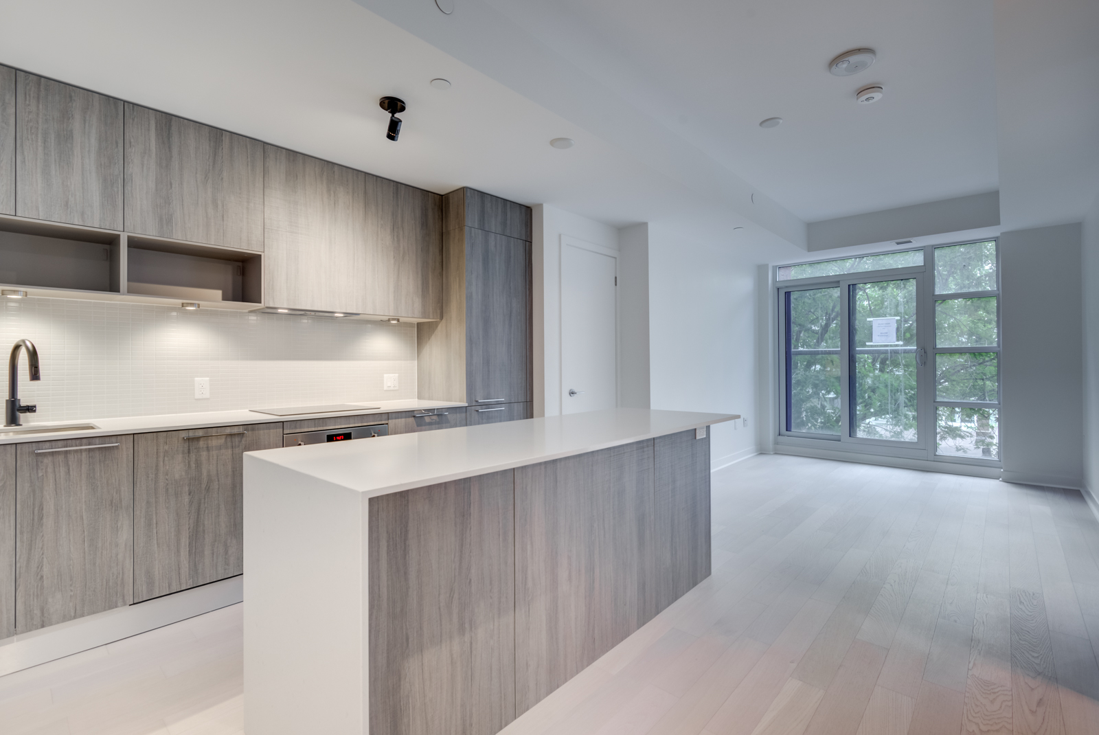 501 Adelaide St W Unit 408 – empty kitchen, dining and living room with light laminate floors and walls.