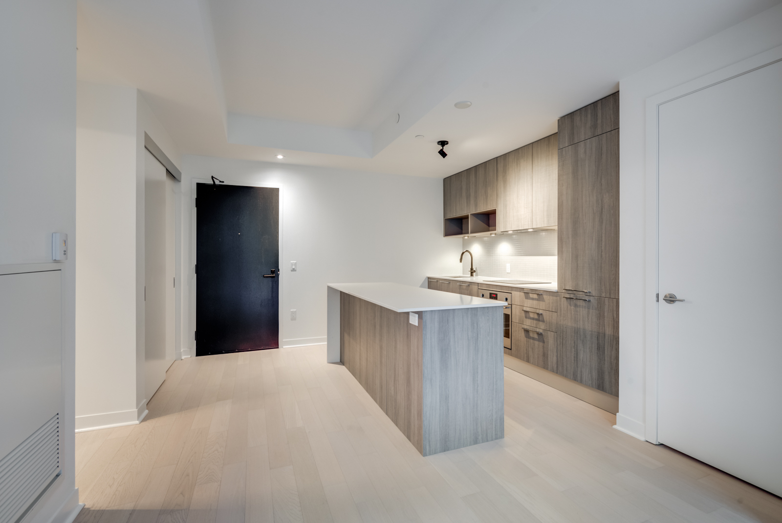 Light-toned laminate floors, kitchen island with wooden base and cabinets with wood finishes.