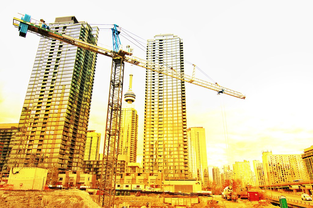 Construction crane and buildings in downtown Toronto in yellow filter.