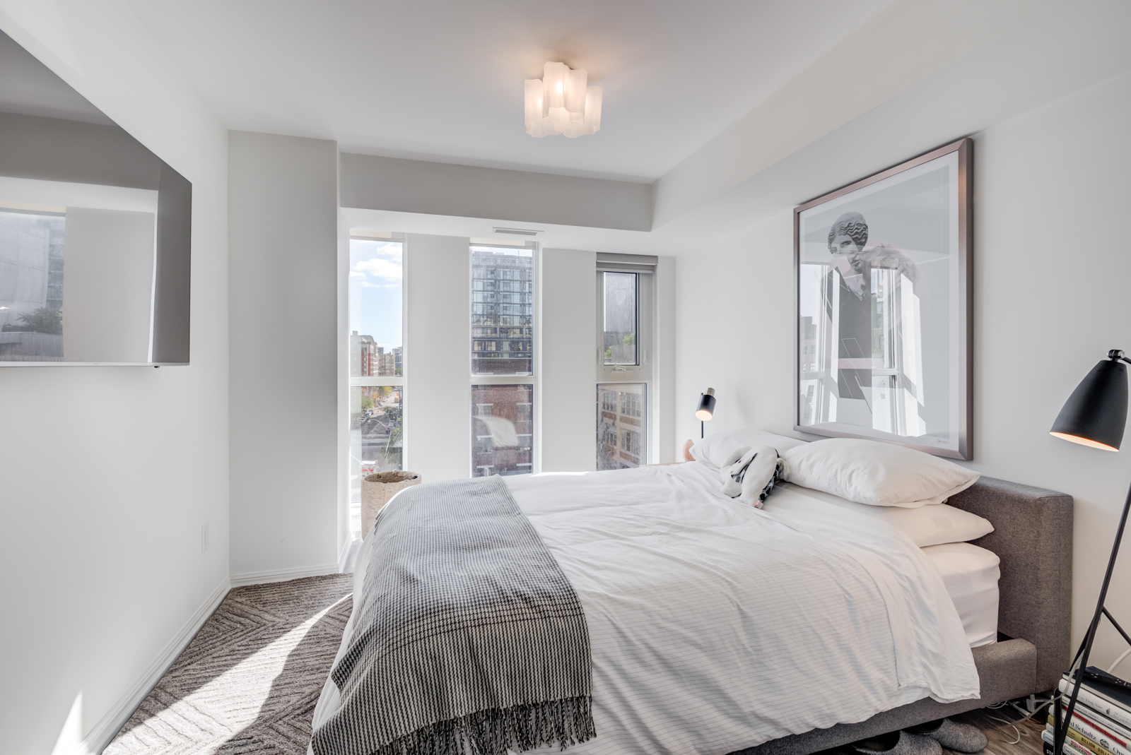 Sunny gray and white master bedroom with large bed.