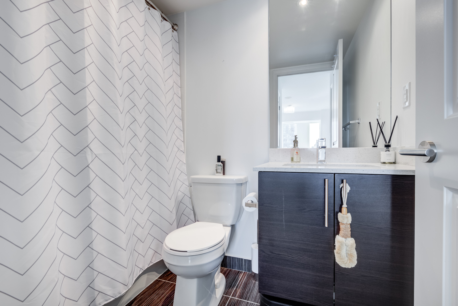 Master bath with closed white curtain, toilet and large vanity.
