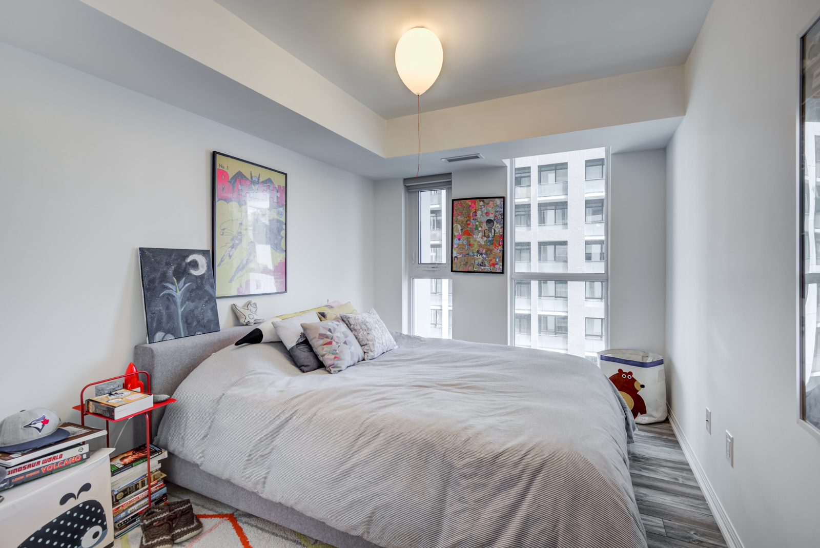 Second bedroom with large bed and windows plus wall art.