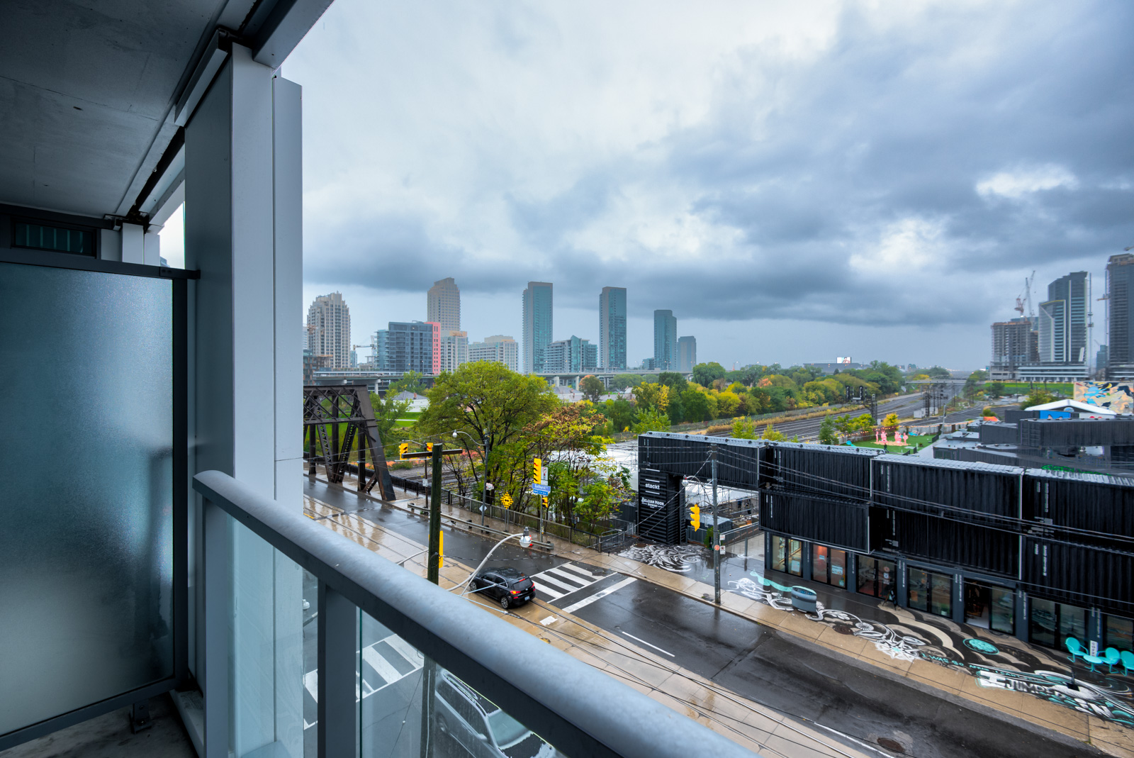 Balcony view from Minto Condos of distant buildings, cloudy skies and slippery, rain-soaked Bathurst St.