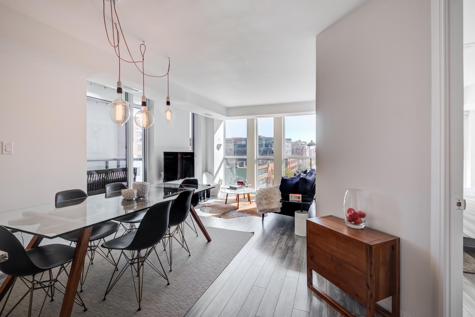 Chic pendant light-bulbs hanging above dining table of 400 Adelaide St E Unit 704 condos in Moss Park.