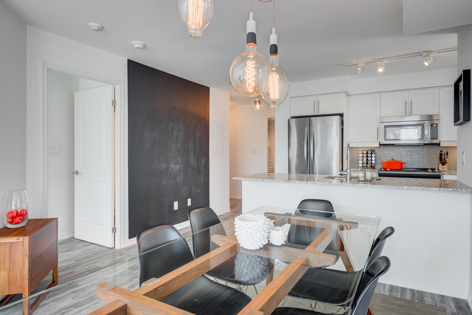 Close up of pendent light-bulbs hanging above dining table and blackboard wall in 400 Adelaide St E Unit 704 in Moss Park.