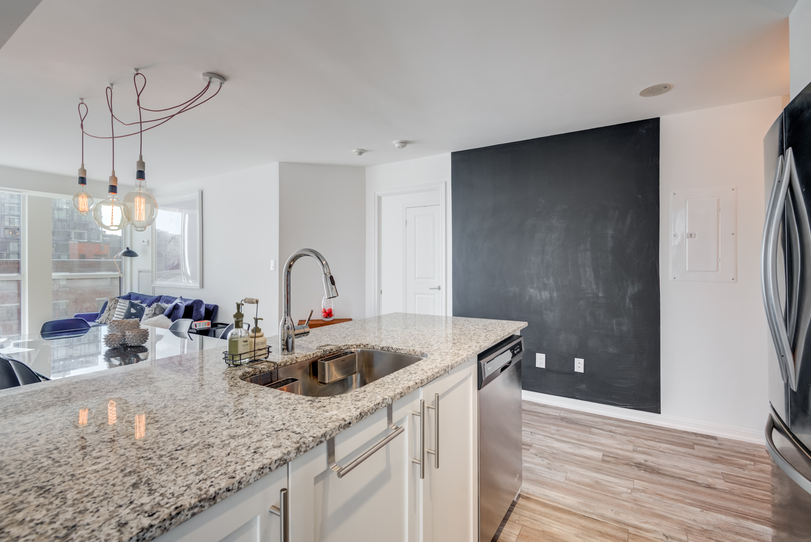 Granite counter-top, chrome faucet and blackboard wall of kitchen at 400 Adelaide St E Unit 704 condos in Moss Park.