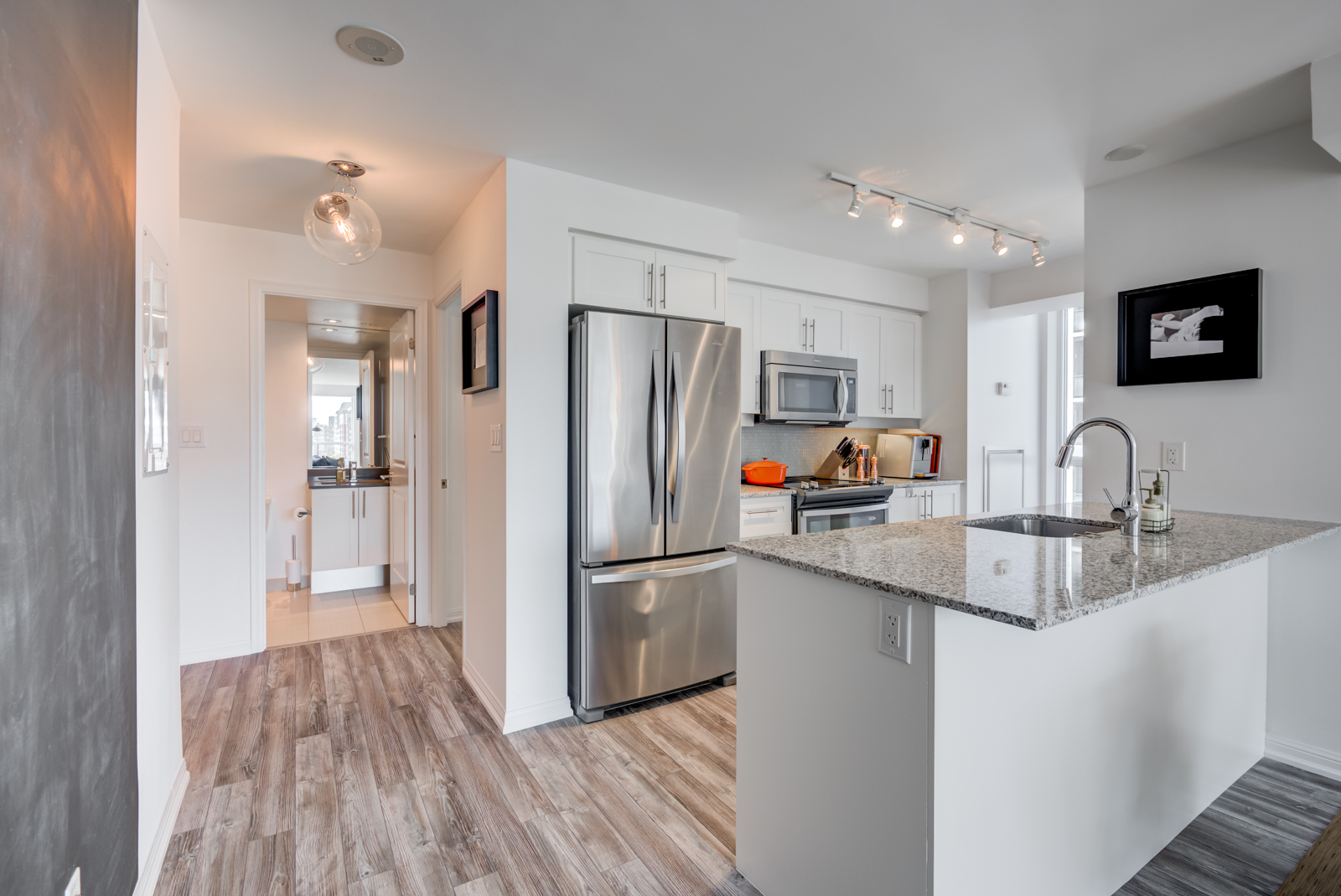 Breakfast bar with granite counter-top and stainless-steel kitchen appliances at 400 Adelaide St E Unit 704 condos in Moss Park.