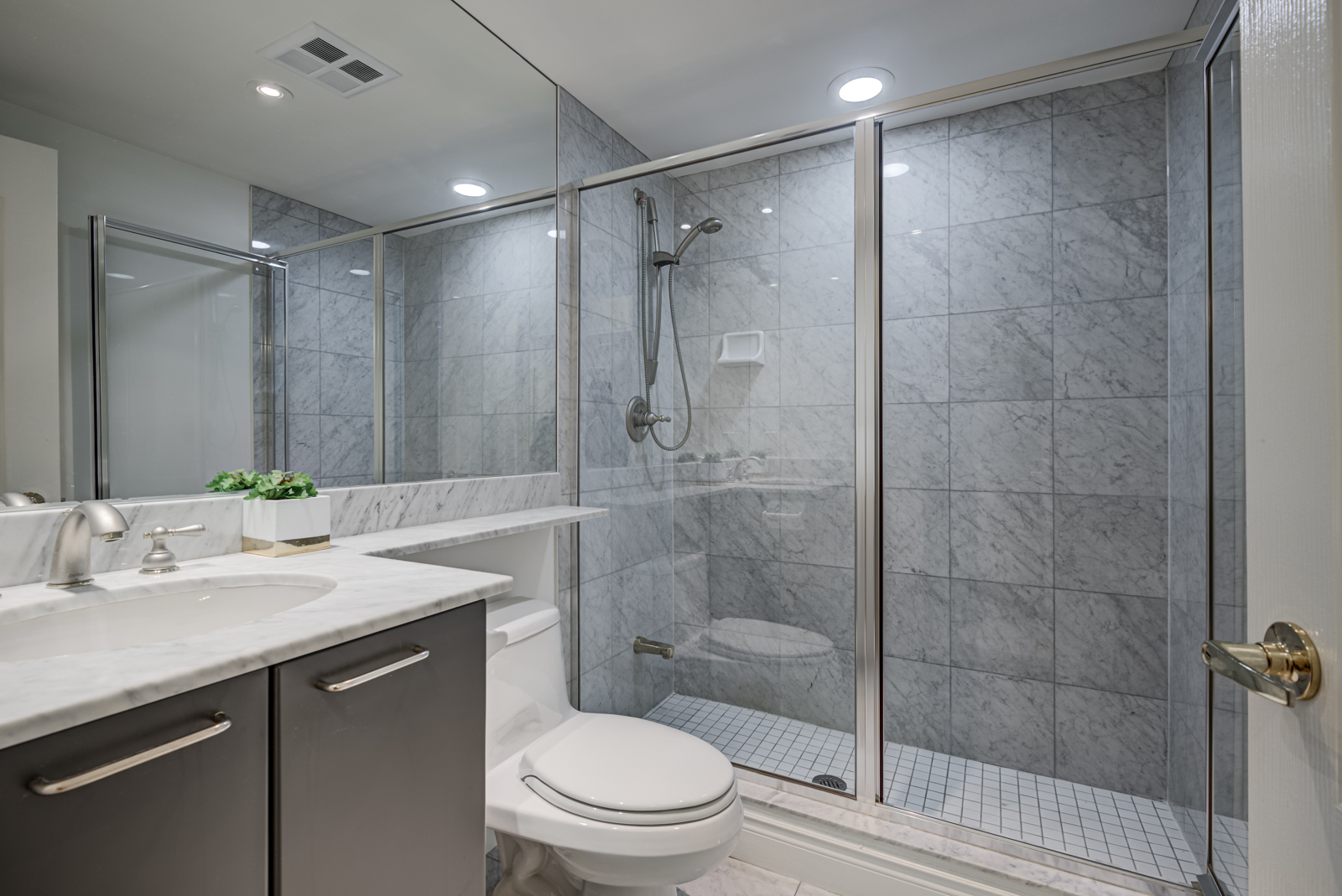 Bathroom in dark grays, lots of glass, and standing shower with detachable showerhead.