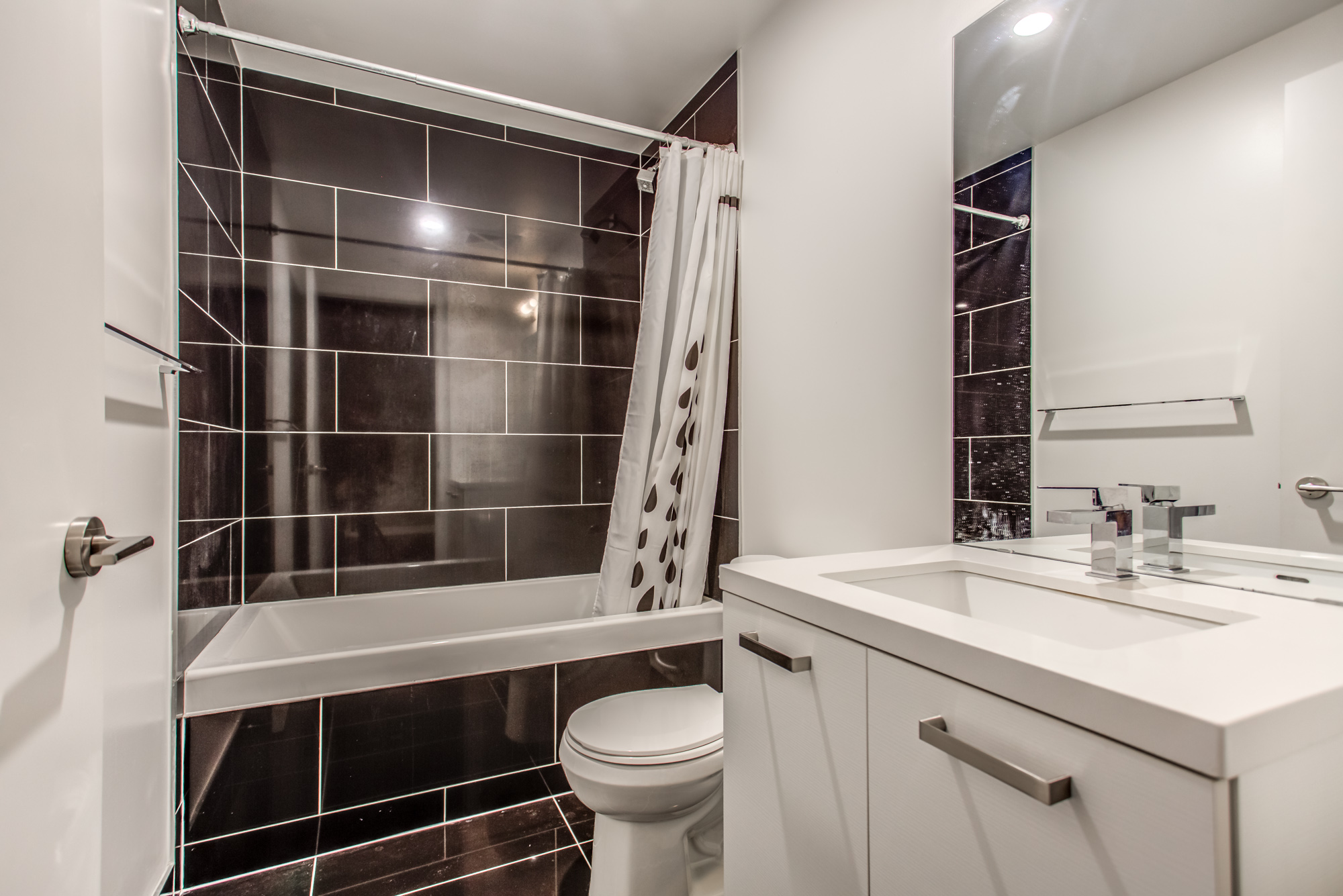 39 Brant St Unit 918 washroom with large, rectangular polished black tiles and gray and white colours.