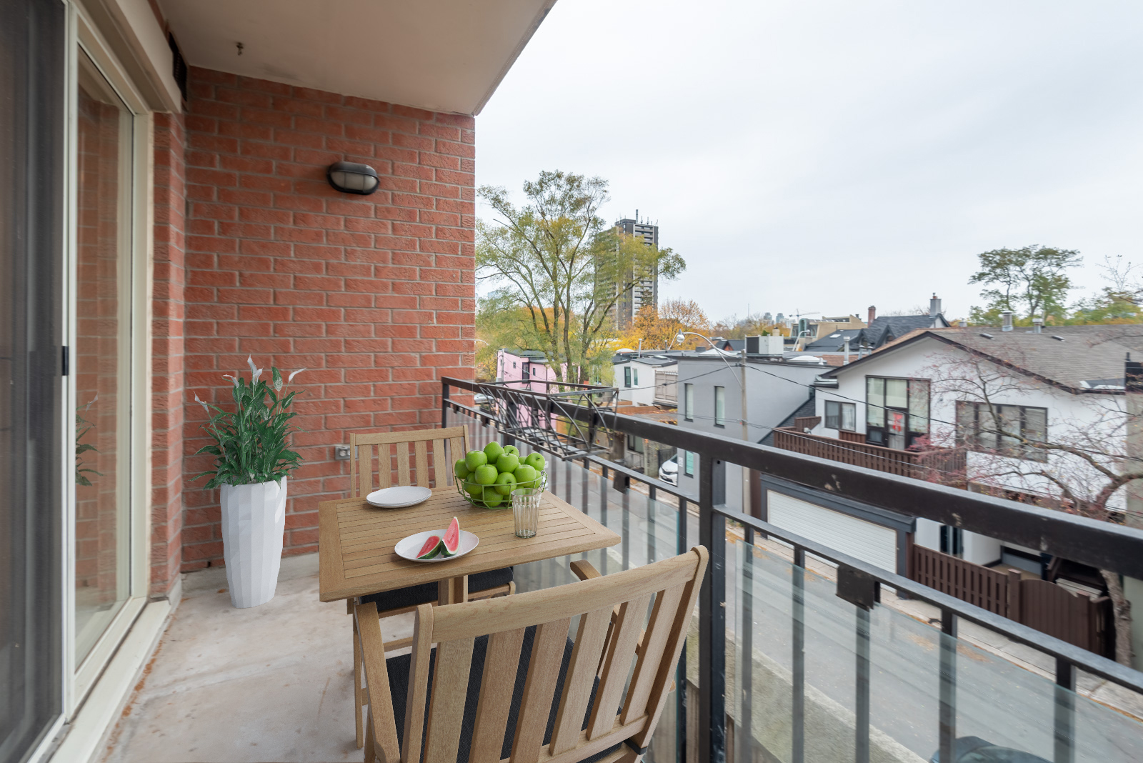 Balcony view of Yorkville streets from McMurrich Residences with 3D table and chairs and fruit.