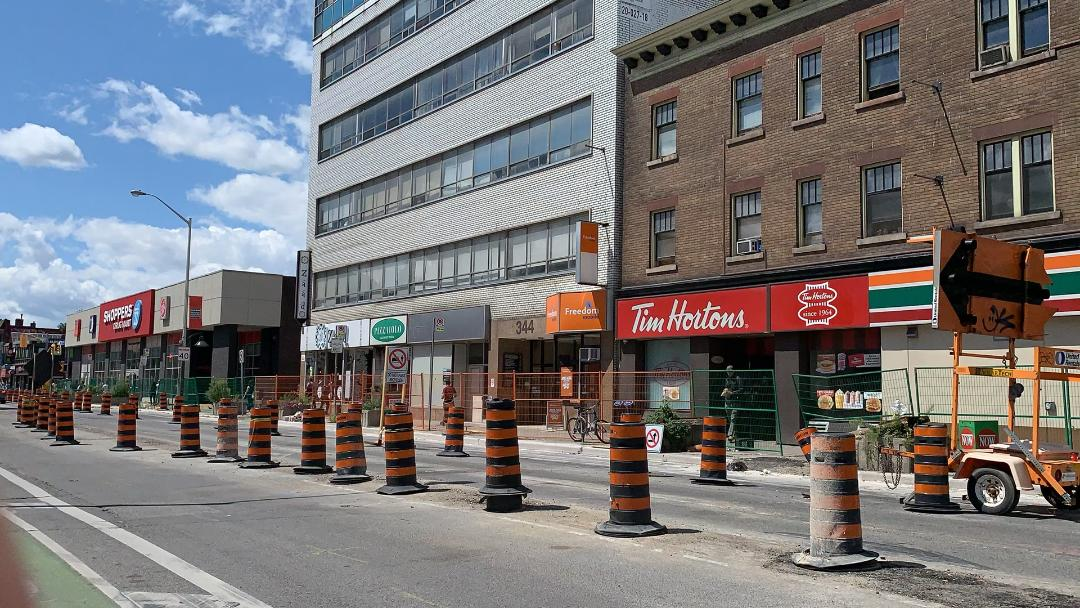 Black and orange construction cones, fence and Tim Hortons storefront on Bathurst and Bloor West in The Annex.