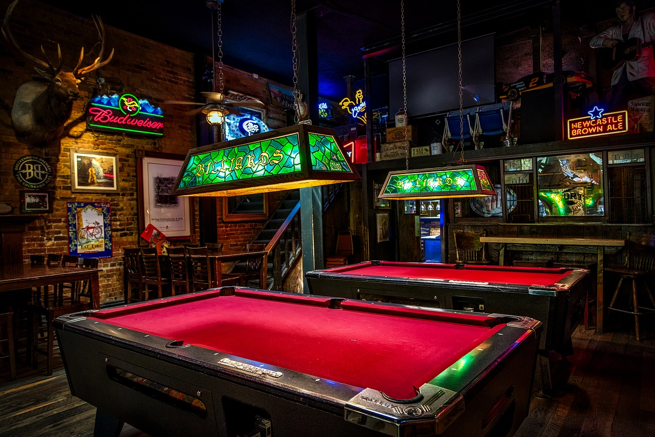 British-style pub with neon beer signs, deer head and billiards tables with red-felt lining.