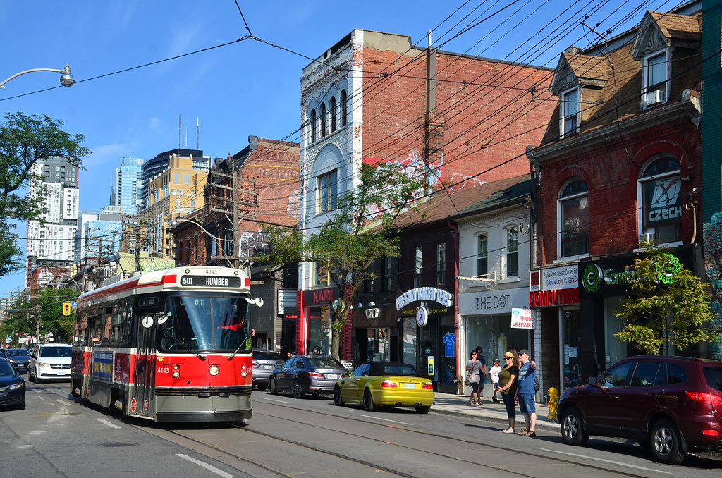 Red streetcar and small shops along Queen West, Toronto.