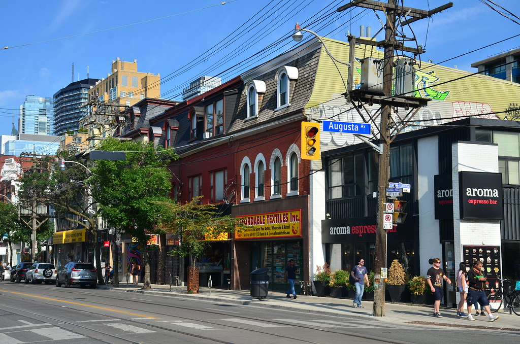 Exterior of Aroma Espresso Bar on Queen West along with other shops and buildings.