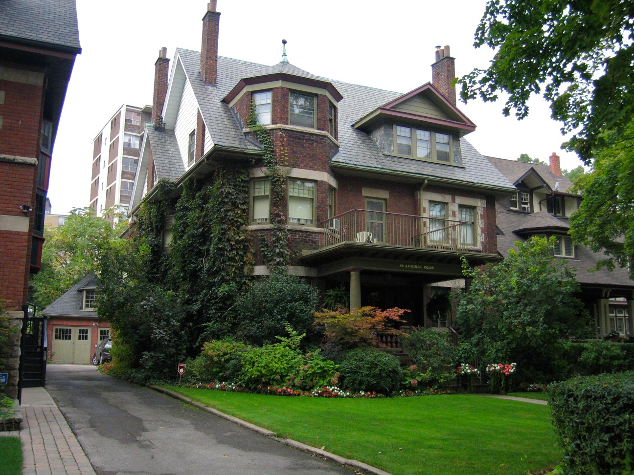 Brown Victorian mansion with green lawn, shrubs and ivy on Bathurst and Bloor West in The Annex neighbourhood.