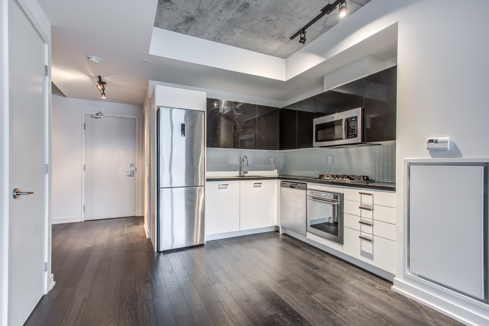 Condo with laminate floors and exposed concrete at 39 Brant St Unit 918, Brant Park Lofts, Queen West.