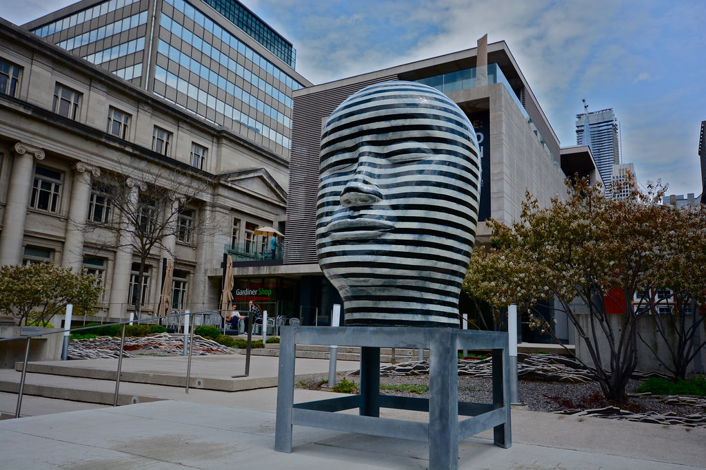 Black and silver striped sculpture of human head outside Gardiner Museum on Bloor West.