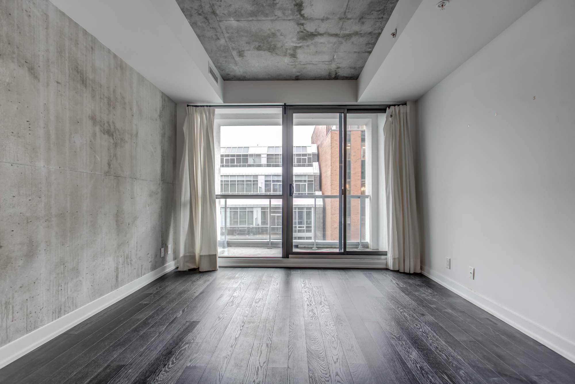 Industrial-style loft with unfinished wall and ceiling on 39 Brant St Unit 918 in Queen West, Brant Park Lofts.