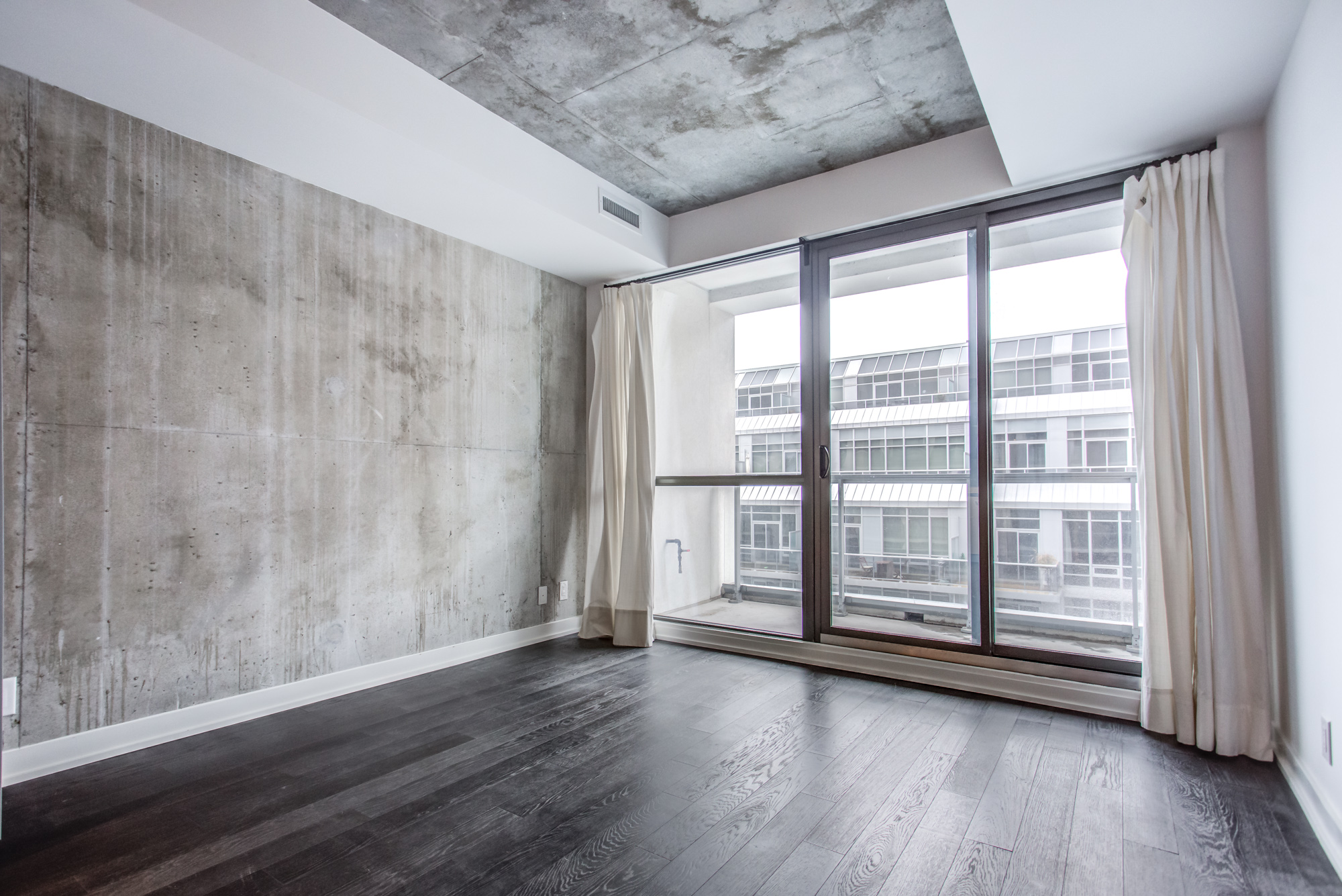 39 Brant St Unit 918, Brant Park Lofts, in Queen West with huge windows and exposed concrete wall and ceiling.