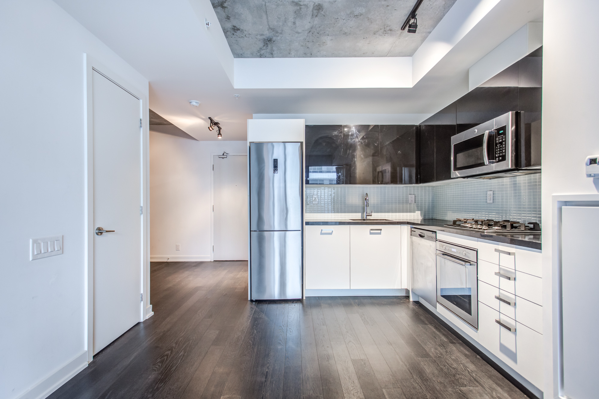 L-shaped kitchen with modern appliances at 39 Brant St Unit 918, Brant Park Lofts, in Queen West.