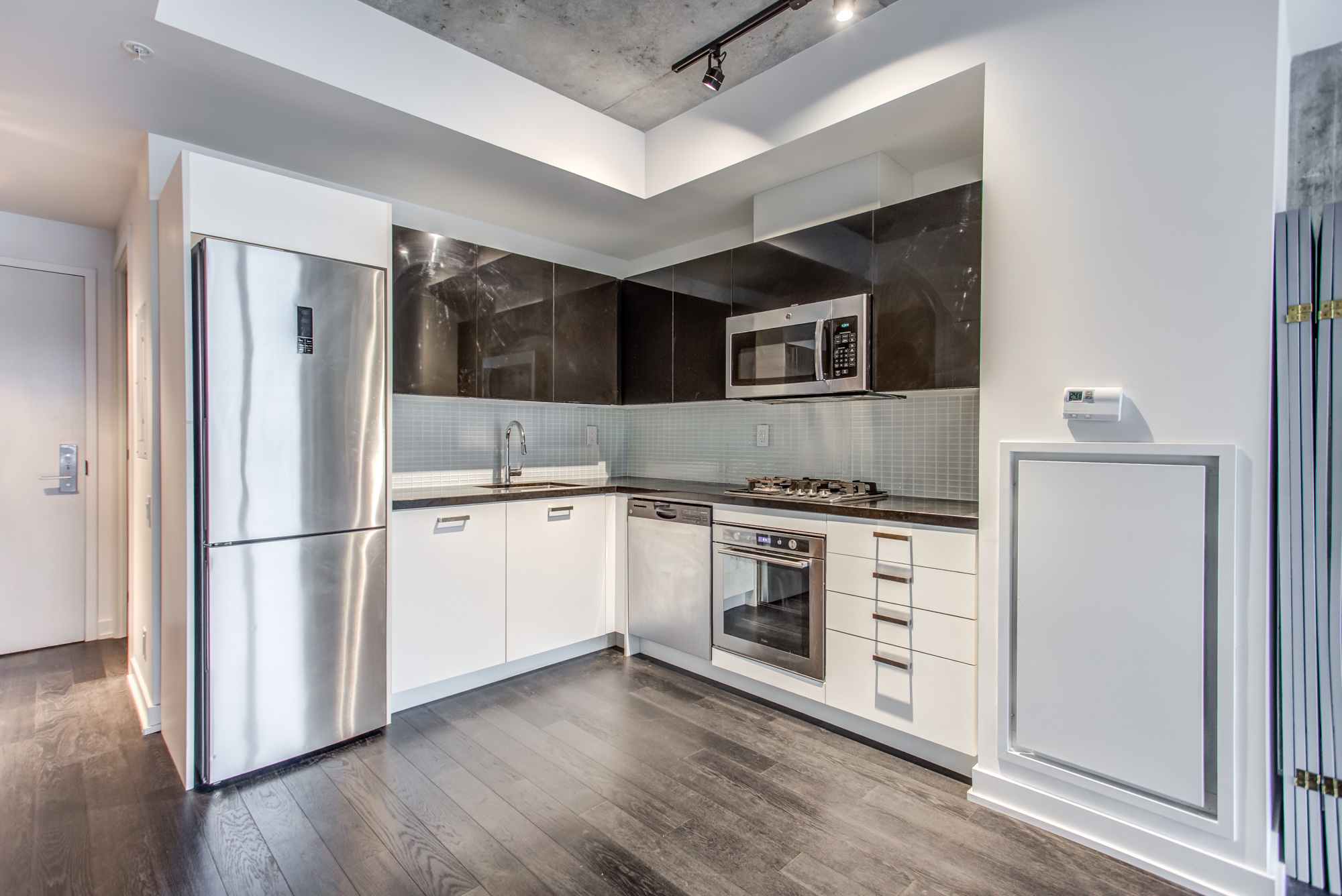 Black and white cabinets and stainless-steel appliances at 39 Brant St Unit 918, Brant Park Lofts, in Queen West.