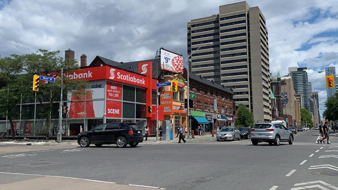 Signs and billboards for Scotia Bank and Pizza Pizza along Bathurst and Bloor West in The Annex neighbourhood.