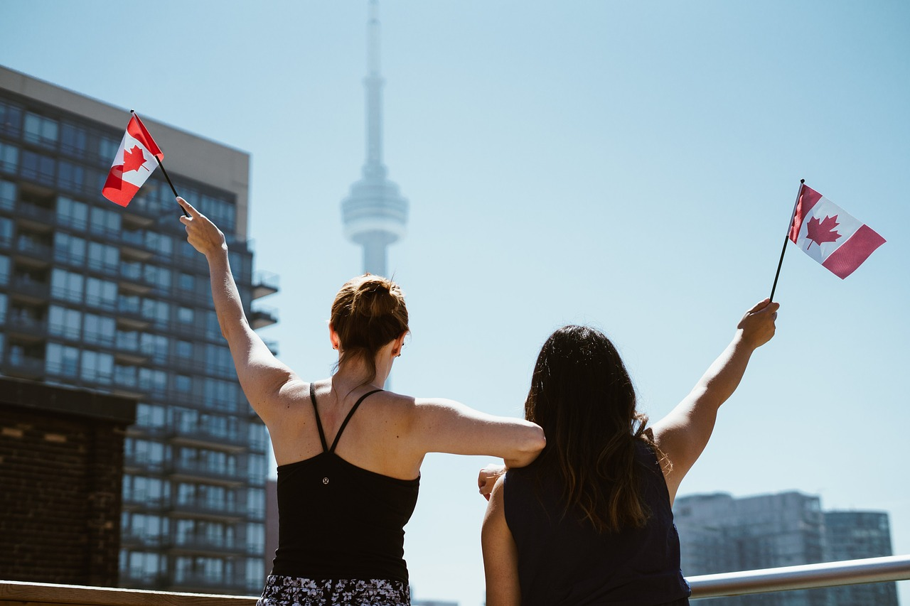Girls waving Canadian flags in front of the CN Tower in Toronto.