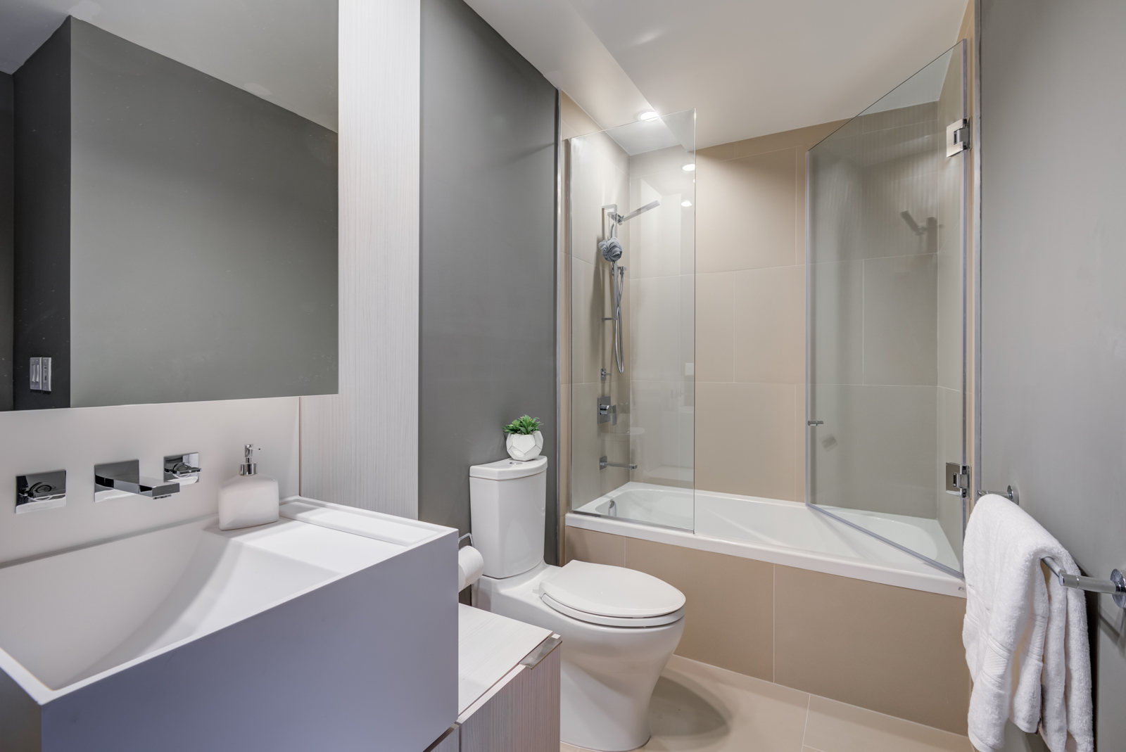 Master bath of 1 Bloor St E Unit 4305 with tub, shower, white sink bowl, and detachable showerhead.