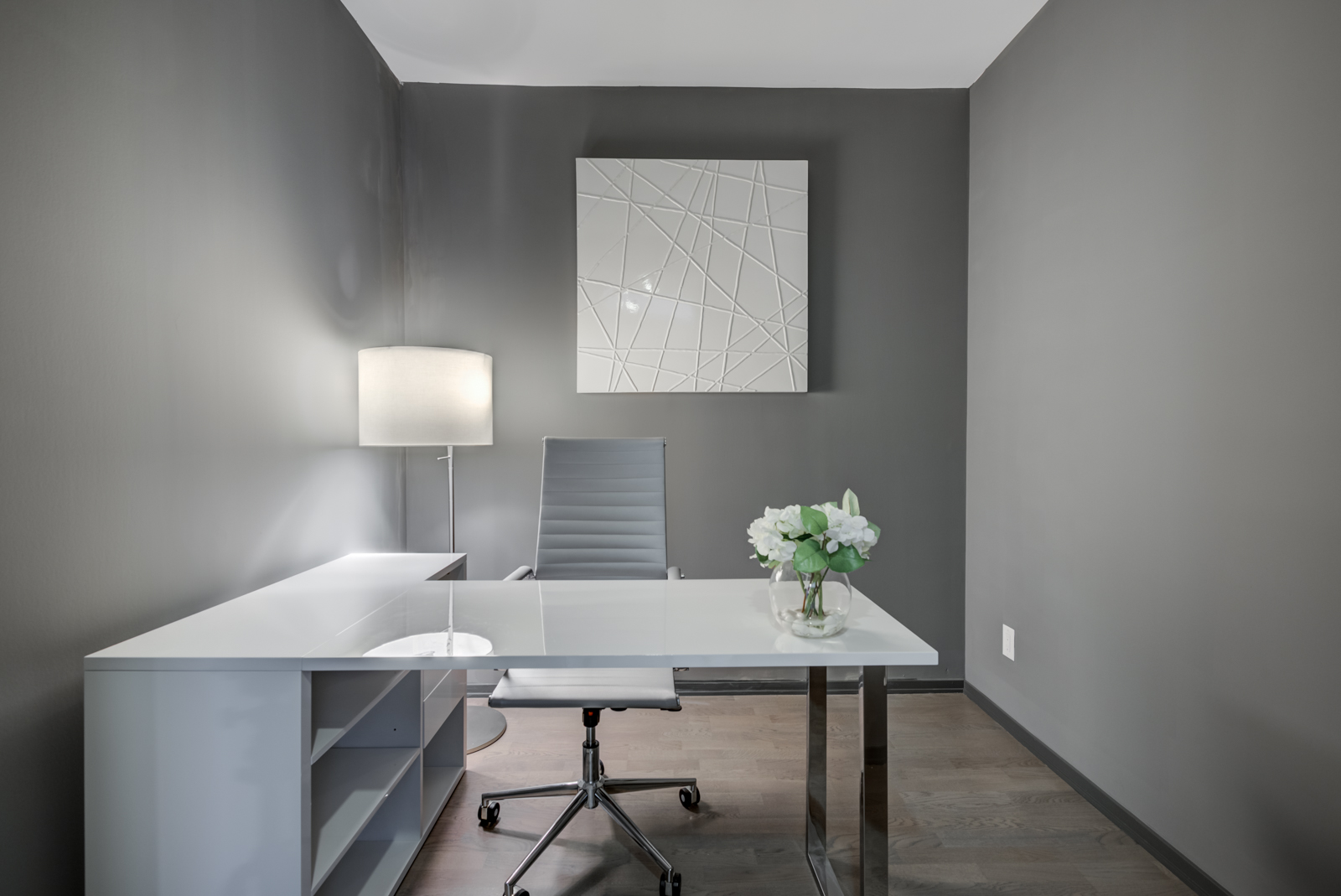 Den with dark gray walls, white desk, gray chair and single lamp.