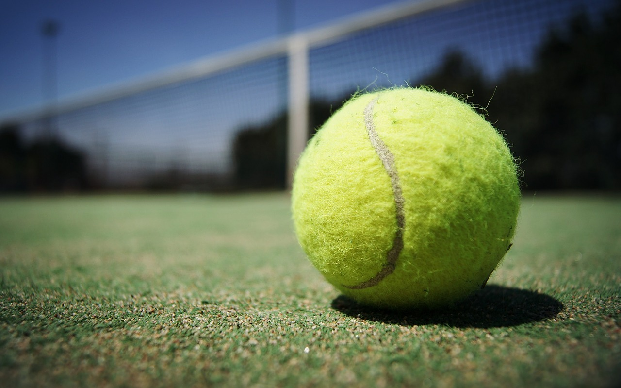 Close up of green tennis ball lying on ground.