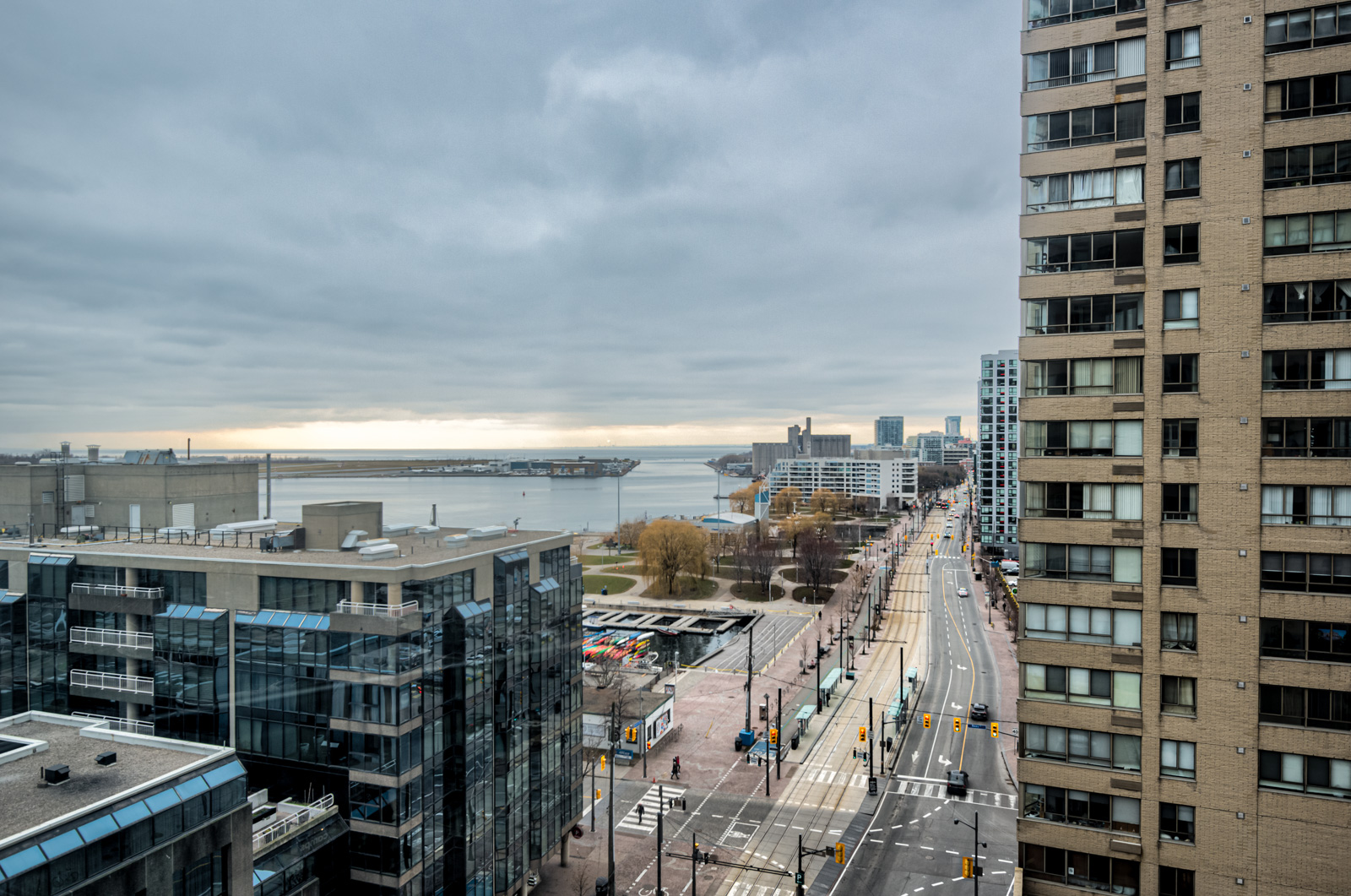 Balcony view of Lake Ontario, buildings, streets, cars and Billy Bishop Airport in distance.
