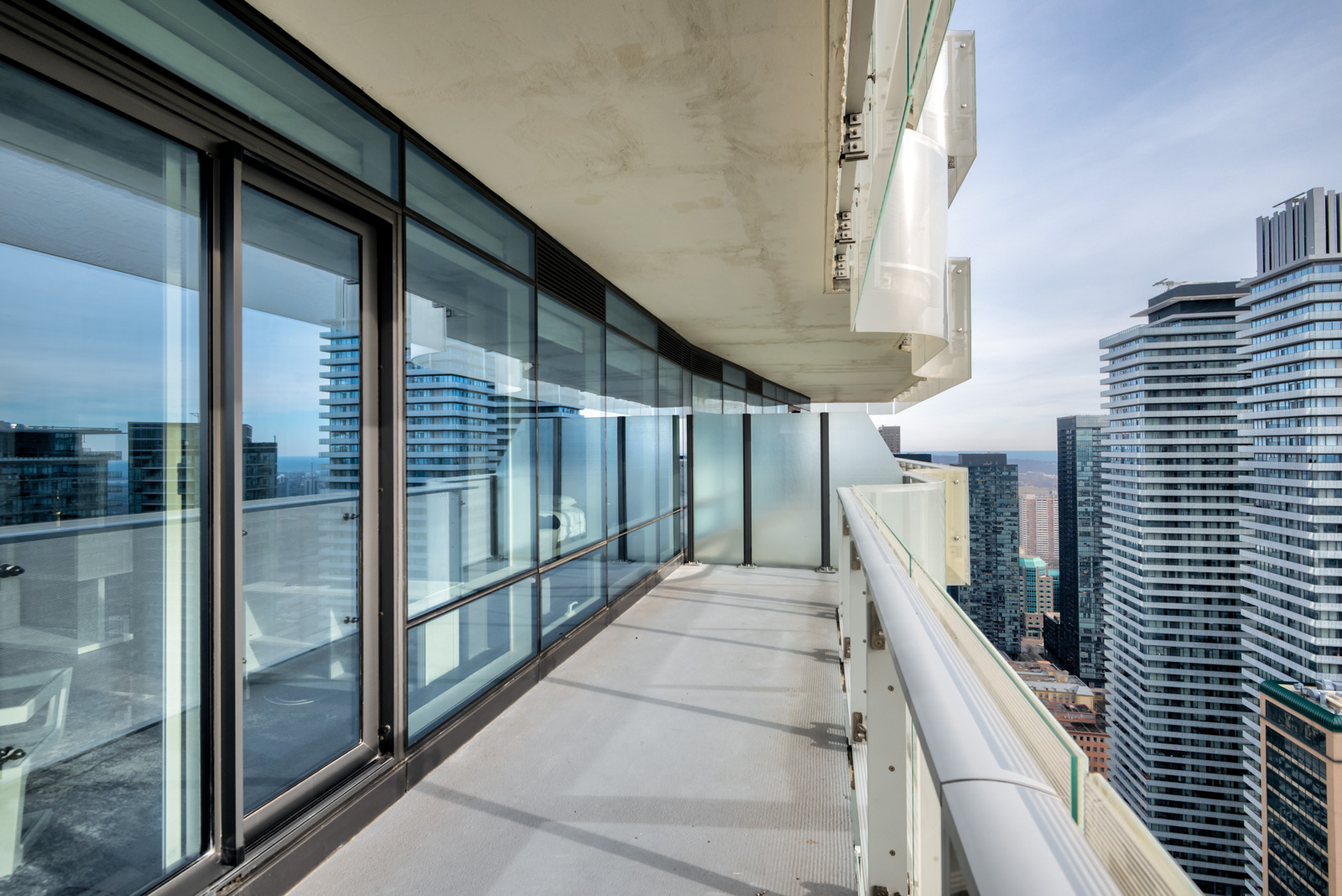 Daytime view of balcony with distant view of CN Tower from One Bloor Condos.
