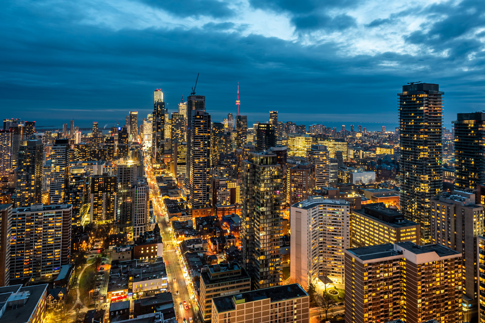 Balcony view of golden lights along Toronto skyline and Yonge and Bloor at night from One Bloor Condos.