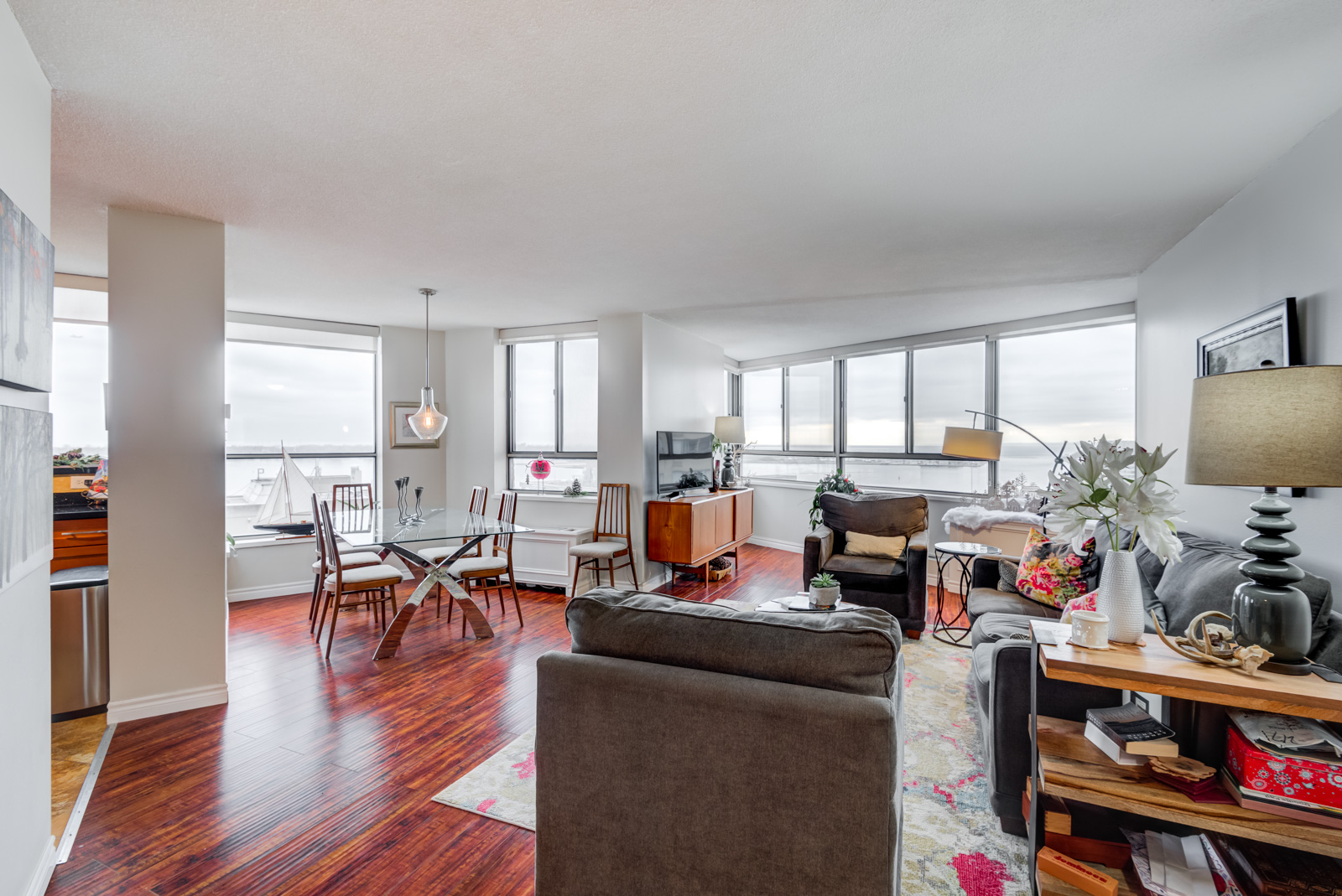 260 Queens Quay W Unit 1202 living and dining room with red laminate floors and huge windows.