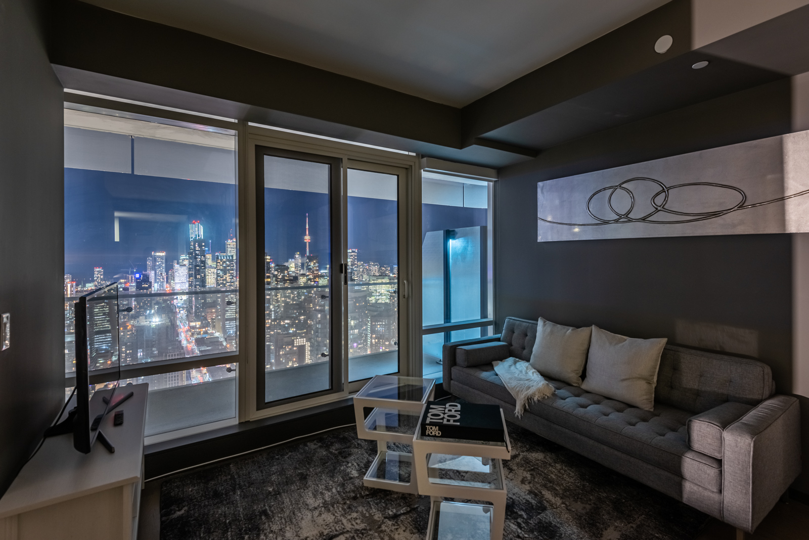Living room at night with view of Toronto skyline through windows of 1 Bloor St