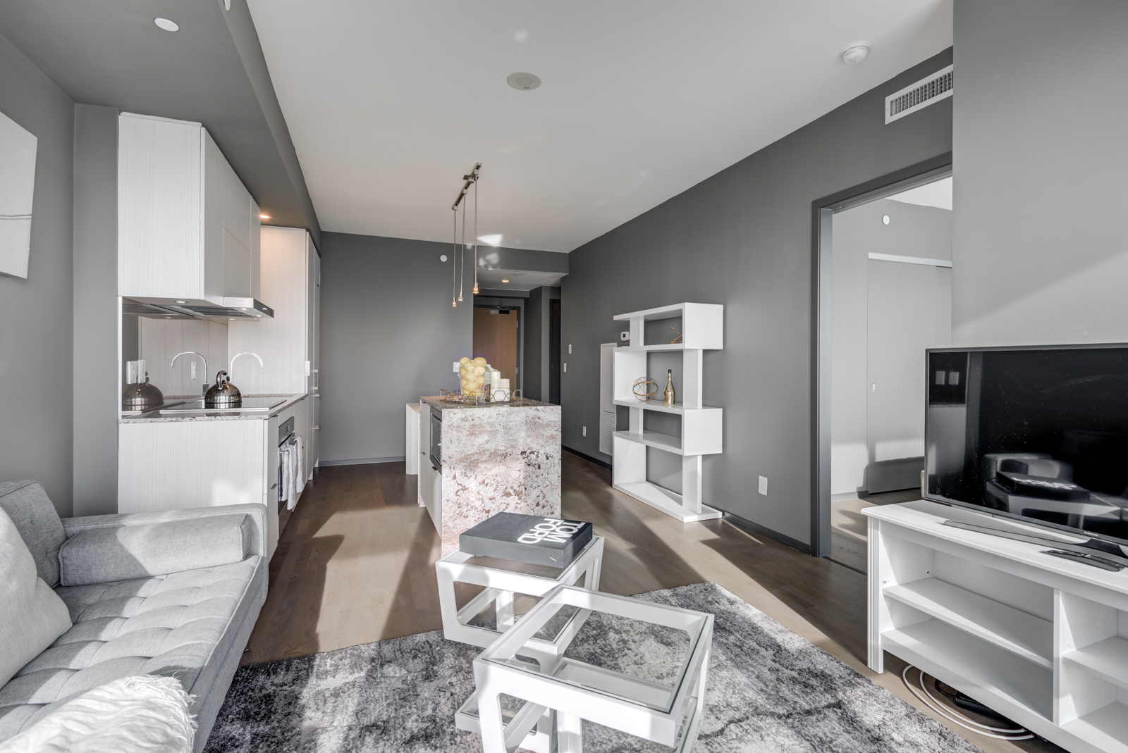 Open-concept living room and dining room with hardwood floors at 1 Bloor St E Unit 4305 (One Bloor Condos).